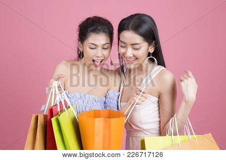 Portrait Of Two Beautiful Asian Smiling Young Women With Shopping Concept. Woman Holding Shopping Ba