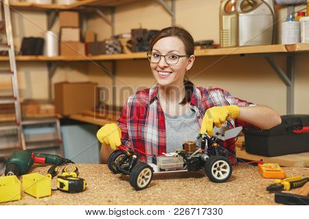 Young Woman In Plaid Shirt, Gray T-shirt, Yellow Gloves Making Toy Car Iron Model Constructor, Worki