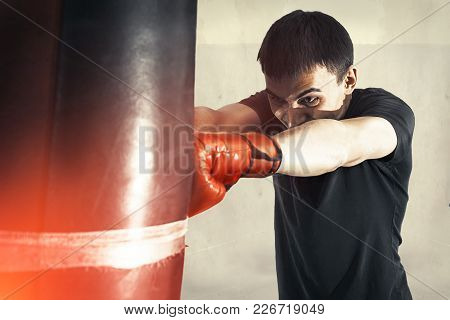 Man Boxing Strikes Punching Bag, Angry, Tense. Isolated Toned Background