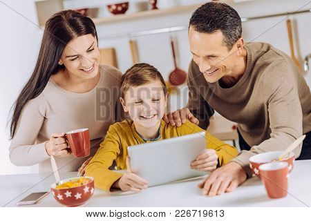 Pleasant Morning. Adorable Pre-teen Boy Watching A Video On Tablet Together With His Loving Parents