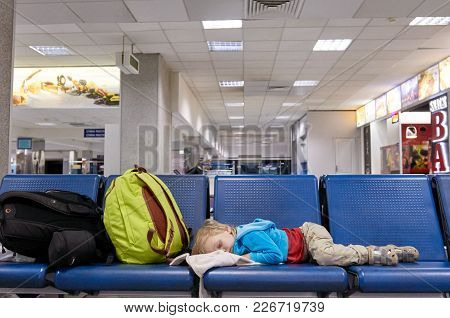 Tired Little Boy Sleeping On Chair While Waiting Flight At The Airport. Kiev, Ukraine, Borispol Airp