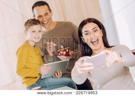 Love My Boys. Upbeat Young Woman Taking A Selfie Of Herself And Her Husband And Son While They Havin