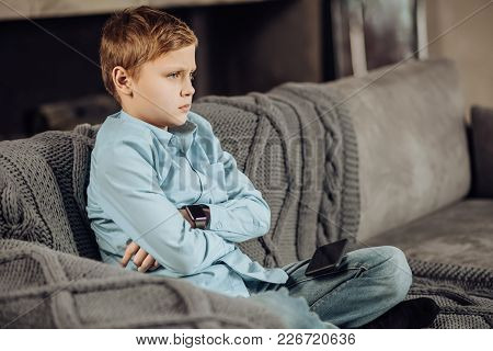Down In Dumps. Cute Pre-teen Boy Sitting Cross-legged On The Sofa And Folding His Arms Across His Ch