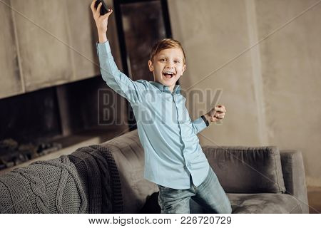 Great Achievement. Upbeat Pre-teen Boy Kneeling On The Sofa And Raising His Hands In A Gesture Of Tr