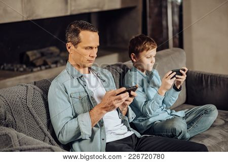 Paying No Attention. Pleasant Young Man And His Pre-teen Son Sitting On The Sofa Next To Each Other
