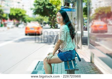 Girl Waiting For Public Transportation At Bus Stop