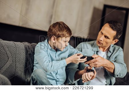 Getting Aggressive. Irritated Young Father And Son Sitting On The Couch And Fighting Over A Phone, E