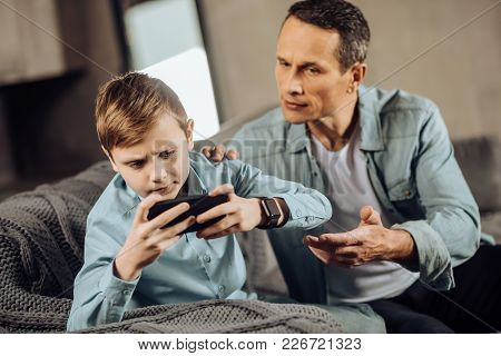 It Is Enough. Strict Young Father Trying To Make His Son Stop Playing On His Phone, Reaching Out His