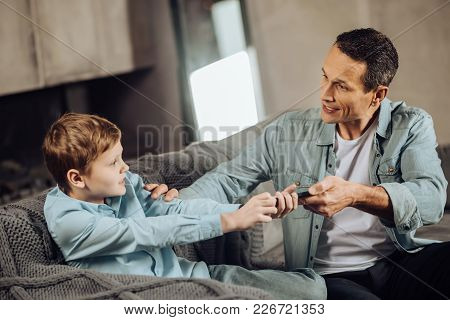 Lack Of Understanding. Strict Young Father Taking Away The Phone From His Sons Hands, Trying To Make