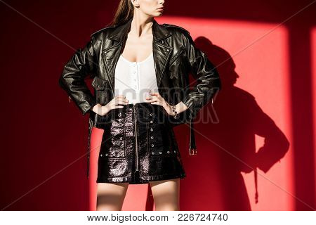 Cropped View Of Girl Posing In Black Leather Jacket For Fashion Shoot On Red