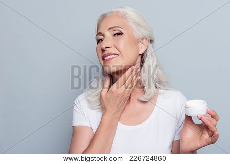 Mature Adult Senior Woman With Gray Hair Is Taking Care About Her Face And Neck, She Is Smearing Nat