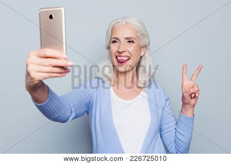 Portrait Of Happy Excited Cheerful Joyful Funny Grandmother Grandma Granny Showing Tongue And Two Fi