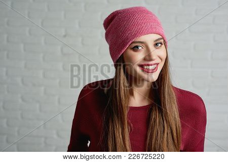 Studio Portrait Of A Young Smiling Model, Wearing Pink Cap And Red Sweatshot. Also She Has Light Dai