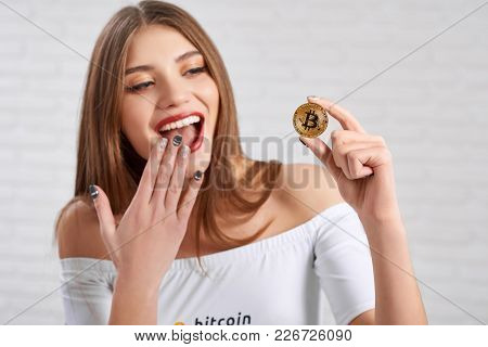 Young Beatiful Girl Wearing White Top With Open Shoulders And Red Lipstick Keeps Golden Bitcoin In F