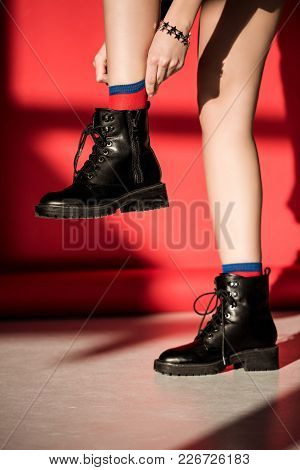 Low Section Of Girl Posing In Black Shoes On Red