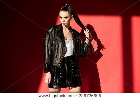 Beautiful Girl With Ponytail Hairstyle Posing In Black Leather Jacket For Fashion Shoot On Red