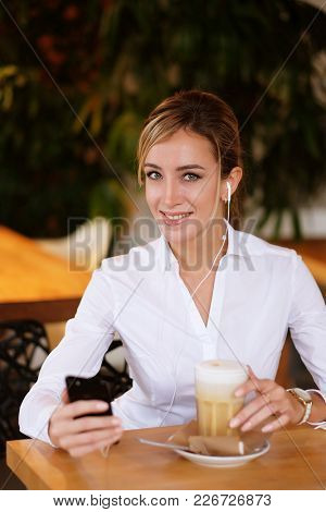 lifestyle and people concept: Woman using mobile phone at cafe