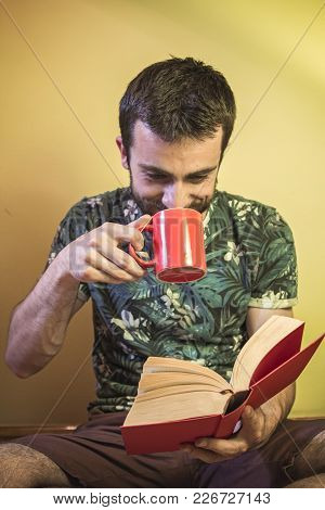 Young Attractive Man Reading A Book And Drinking Some Beverage From A Cup, Tea Or Coffee