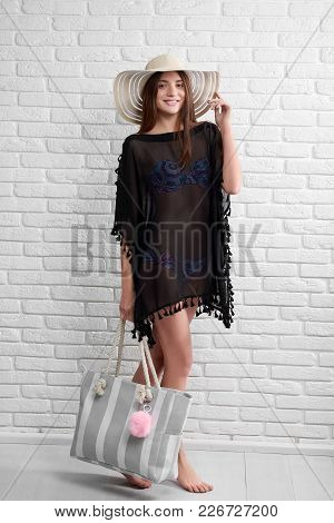 Pretty Smiling Girl Wearing Black Translucent Pareo, Colorful Patterned Swimwear And A Beige Hat Wit