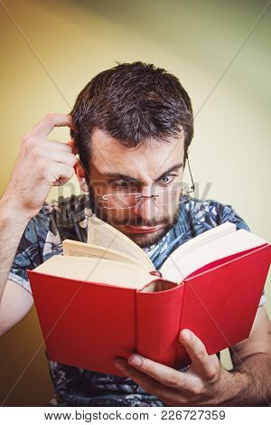 Young Man With Glasses Having Troubles Reading Close And Small Letters