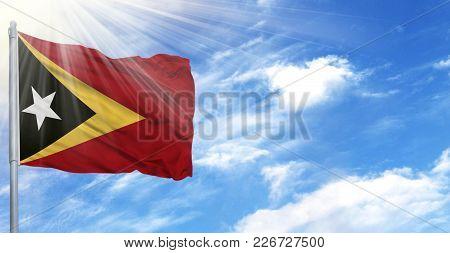Flag Of East Timor On Flagpole Against The Blue Sky.