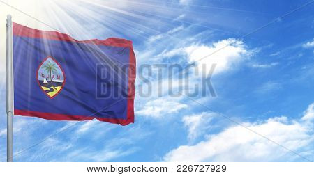 Flag Of Guam On Flagpole Against The Blue Sky.