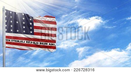 Flag Of Bikini Atoll On Flagpole Against The Blue Sky.