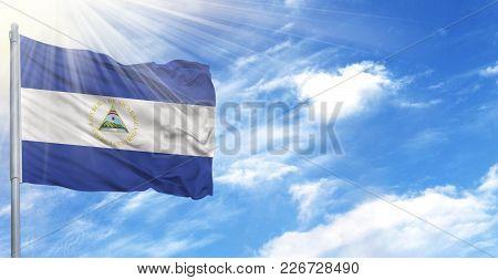 Flag Of Nicaragua On Flagpole Against The Blue Sky.