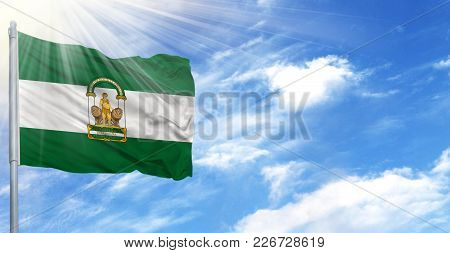 Flag Of Andalusia On Flagpole Against The Blue Sky.