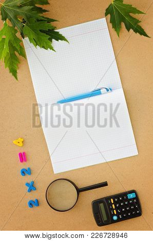 School Desk With Notebook, Pen, Calculator, Magnifier And Numbers. Back To School Concept. Top View
