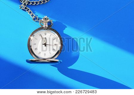 A Vintage Pocket Watch Shows Twelve Hours On A Blue Background. Top View