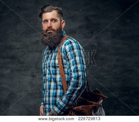 Studio Portrait Of Bearded Male With Tattoo On Arm, Dressed In A Blue Fleece Shirt Holds Backpack.