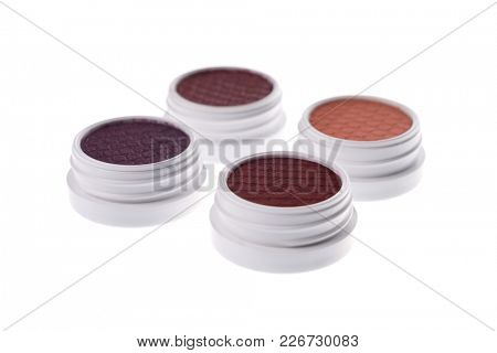 Set of brown eye shadows, selective focus on first one, isolated on white background