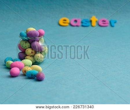 A Small Glass Container Filled With Colorful Speckled Eggs And The Word Easter On A Blue Background