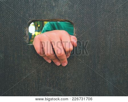 Children Hand Holds A Hole On The Wooden Climbing Wall. Short Fingers Hold Through Board Ladder