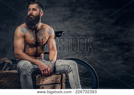 Shirtless Bearded Male With Tattooed Torso Sits On A Wooden Box.