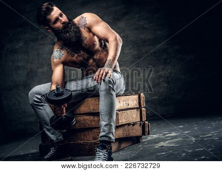 Shirtless Bearded Male With Tattooed Torso Sits On A Wooden Box And Holds Dumbbell.