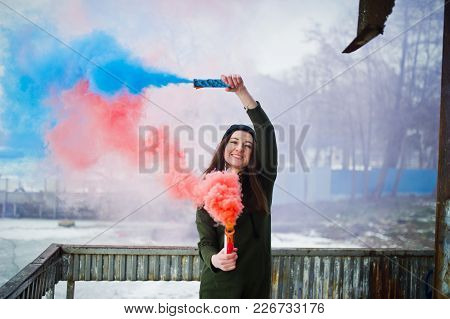 Young Girl With Blue And Red Colored Smoke Bomb In Hands.