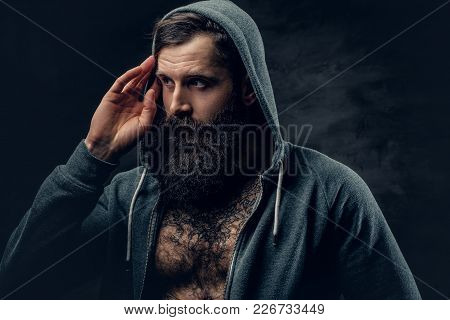 Portrait Of Brutal Bearded Male With Tattoo On A Chest, Dressed In A Grey Hoodie.
