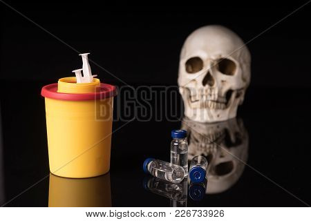 Skull, Syringe And Yellow Waste Container, Isolated On Black With Glossy Reflection