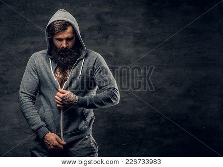 Studio Portrait Of Athletic Bearded Male In A Grey Hoodie.