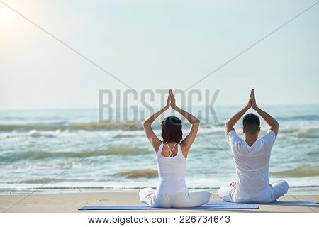 Rear View Of Young Couple Enjoying Yoga Practice On The Beach