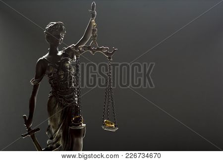 Divorce Concept. Wedding Rings And Statue Of Justice Themis.