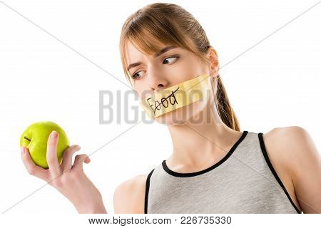 Young Woman With Stick Tape With Striked Through Word Food Covering Mouth Looking At Apple In Hand I