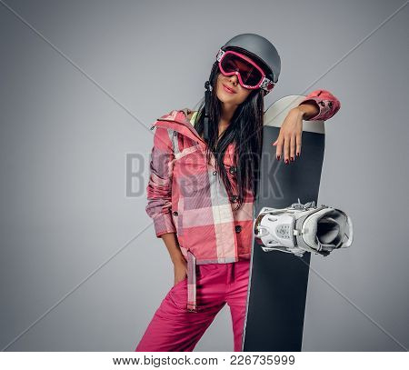 Portrait Of Active Female In A Pink Ski Costume Holding A Snowboard. Isolated On Grey Background.