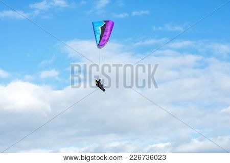 On The Background Of Blue Cloudy Sky Paraglider Pilot Controls The Glider