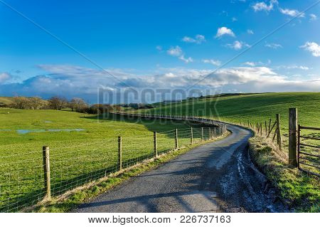 A Winding Country Lane Passing Through Green, Partly Flooded Fields On Farmland. Cumbria, Northern E