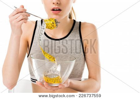 Cropped Shot Of Young Woman Eating Mesuring Tape Isolated On White, Anorexia Concept