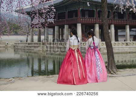 Gyeongbokgung Palace With  Korean National Dress And Cherry Blossom In Spring,seoul,south Korea.