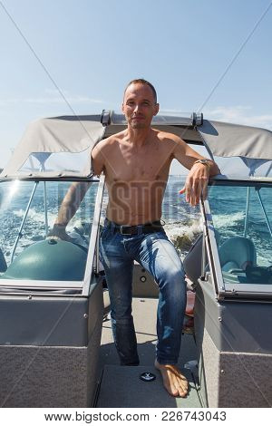 Captain Stands And Driving A Boat Along The River